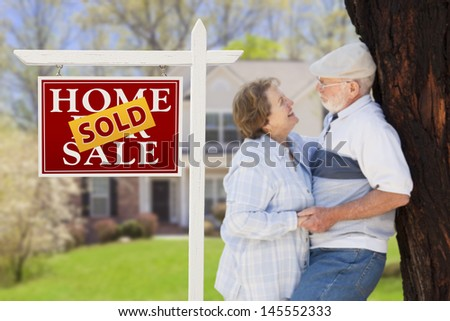 Sold Home For Sale Real Estate Sign with Happy Affectionate Senior Couple Hugging in Front of House. - stock photo