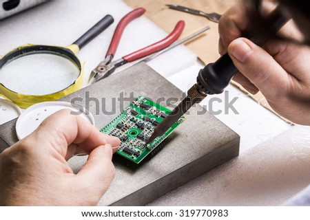 soldering microchips and circuit boards - stock photo