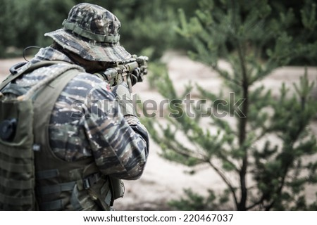 Soldier aiming with rifle - rear view - stock photo