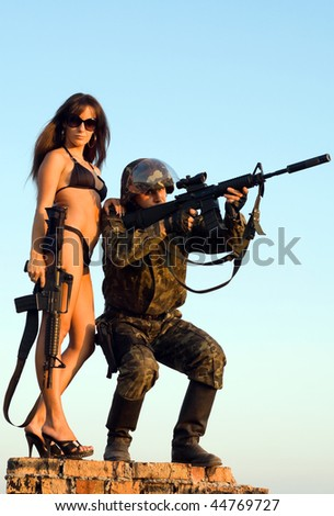 Soldier and woman in bikini staying on the brick wall - stock photo