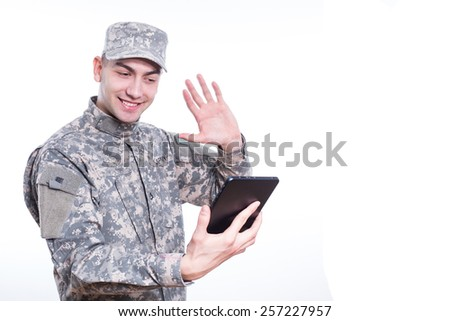 Soldier Calls Home on tablet, Skype - stock photo