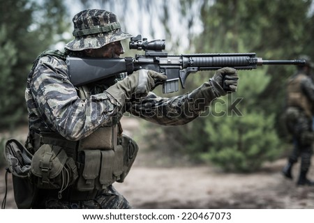 Soldier dressed in tiger stripe camouflage, aiming with assault rifle at target - stock photo