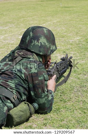 soldier dressed in uniform aims his M16 rifle while on duty - stock photo