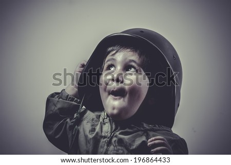 soldier fun and funny child dressed in military cap, playing war games - stock photo