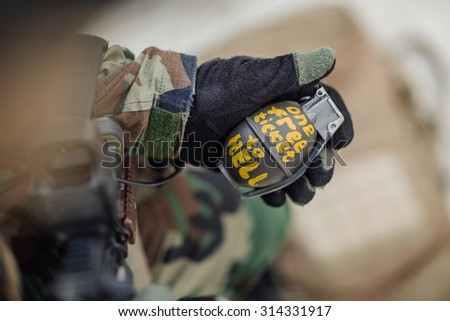 soldier holding a green combat pineapple grenade - stock photo