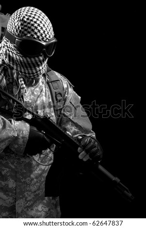 soldier holding a gun, isolated in black, monochrome - stock photo