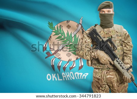 Soldier holding machine gun with USA state flag on background - Oklahoma - stock photo