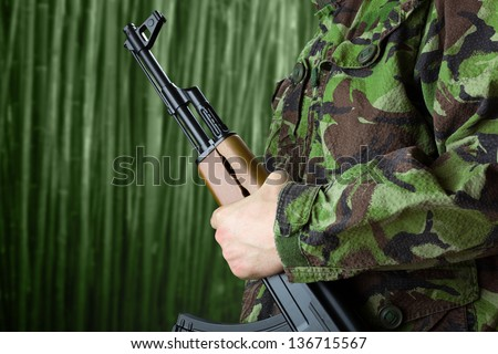 Soldier holding rifle AK-47 against jungle - stock photo