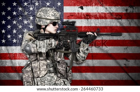 soldier holding rifle on american flag background - stock photo