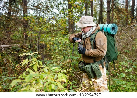 Soldier in a forest with water-bottle. - stock photo