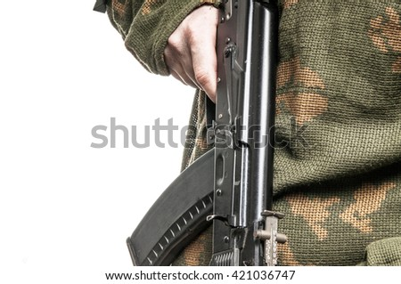 Soldier in camouflage with a gun in his hand - stock photo