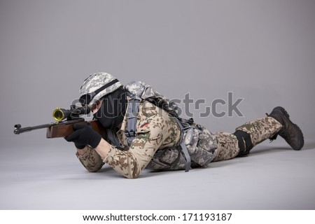 Soldier in camouflage with sniper rifle on the ground - stock photo