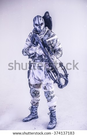 Soldier in the mask with a raven on his shoulder and a crossbow. Fantasy. The post Apocalypse.  - stock photo