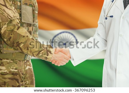 Soldier in uniform and doctor shaking hands with national flag on background - India - stock photo