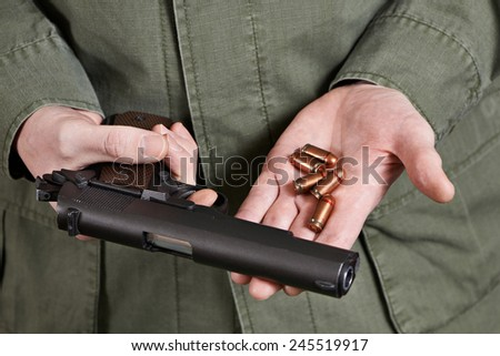 Soldier in uniform holding a gun Colt cartridges to it - stock photo