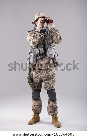 Soldier looking through binoculars in studio - stock photo