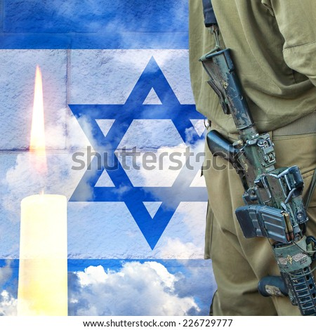 Soldier of Israeli defense forces on Israeli national flag wall and sky background with burning candle  - stock photo