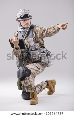 Soldier or commander holding tablet computer and pointing with a finger - stock photo