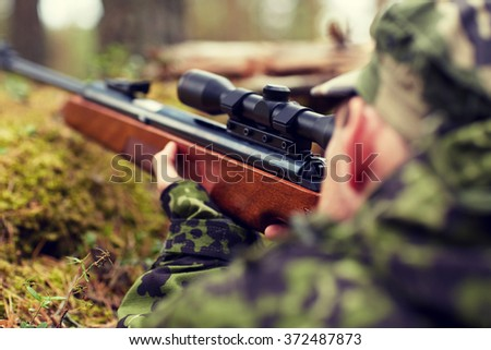 soldier or hunter shooting with gun in forest - stock photo