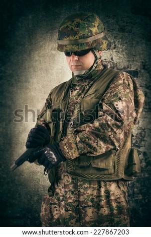 Soldier reloading his gun - stock photo