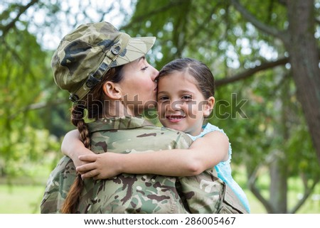 Soldier reunited with her daughter on a sunny day - stock photo
