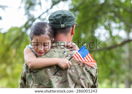 Soldier reunited with his daughter on a sunny day - stock photo