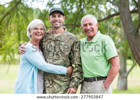 Soldier reunited with his parents on a sunny day - stock photo
