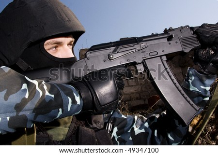 Soldier shooting with an AK47 automatic rifle from covered position - stock photo