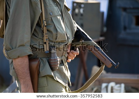 Soldier US patrolling with weapon in recreation wwii / military with machine gun in reenacting ww2 - stock photo