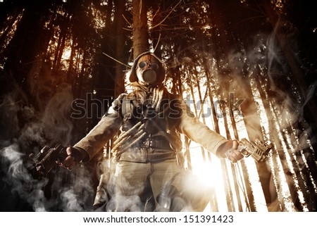 Soldier wearing a gas mask in a forest - stock photo