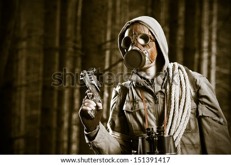 Soldier wearing a gas mask is fighting in a forest - stock photo