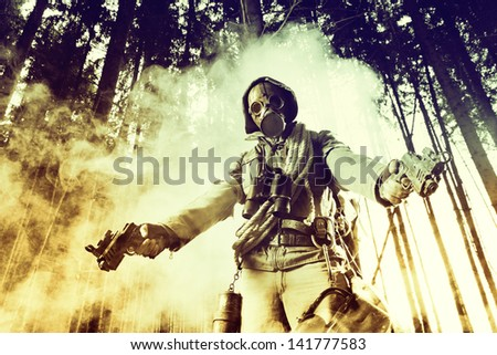 Soldier wearing a gas mask posing with two guns - stock photo