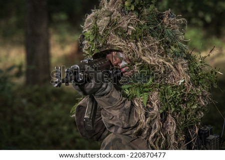 Soldier wearing camouflage, in wood, aiming with sub machine gun - stock photo