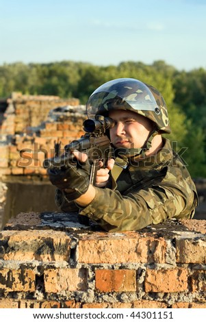 Soldier with a machine gun in camouflage uniform - stock photo