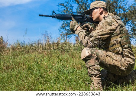 Soldier with a rifle in the field - stock photo