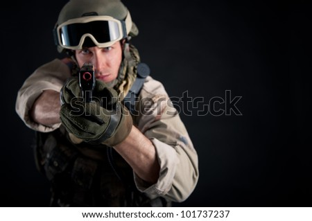 Soldier with gun against black background. - stock photo