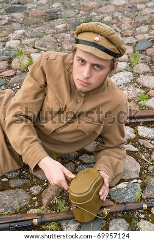 Soldier with gun and boiler in uniform of World War I, resting on the pavement. Costume accord the times of World War I. Photo made at cinema city Cinevilla in Latvia. - stock photo