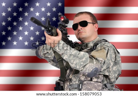 soldier with his assault rifle on flag background - stock photo