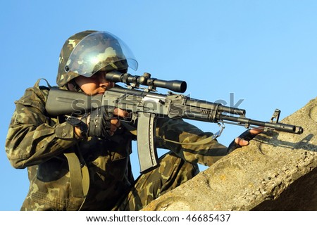 Soldier with machine gun waiting in ambush - stock photo