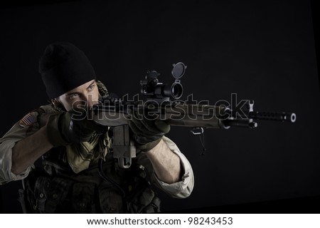 Soldier with rifle against black background. - stock photo