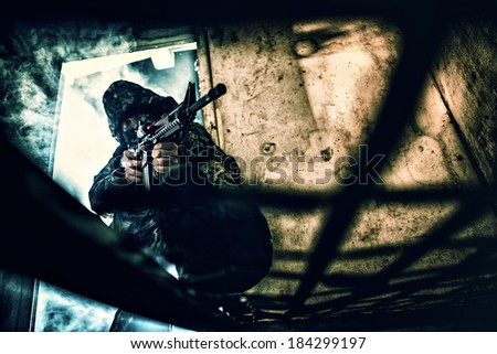 Soldier with rifle aiming with laser sight - stock photo
