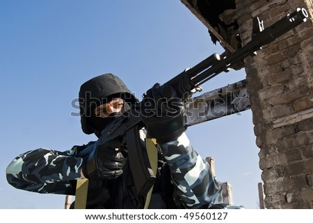 Soldier with russian automatic AK-47 rifle aiming his target - stock photo