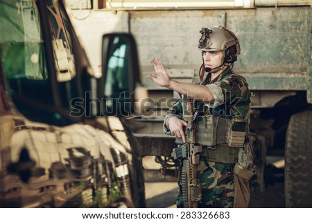 soldiers at the checkpoint stopped a car with his arm - stock photo