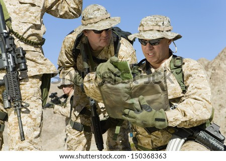Soldiers discussing strategy during war against sky - stock photo
