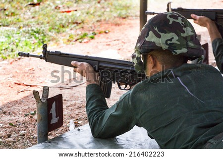 soldiers firing HK33A1 rifle at shooting gallery - stock photo
