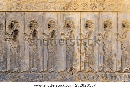 Soldiers of historical empire with weapon. Stone bas-relief in ancient city Persepolis, Iran. Persepolis is a capital of the Achaemenid Empire. UNESCO declared Persepolis a World Heritage Site. - stock photo