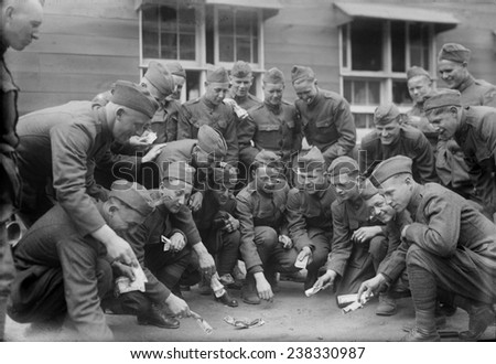 Soldiers playing a dice game, original title: 'Craps at camp', photograph circa 1900s-1930s - stock photo
