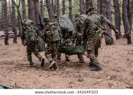 Soldiers run away from the battlefield with stretcher and wounded soldier - stock photo