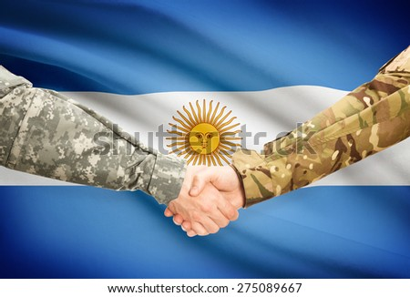 Soldiers shaking hands with flag on background - Argentina - stock photo