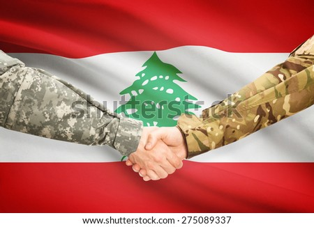 Soldiers shaking hands with flag on background - Lebanon - stock photo